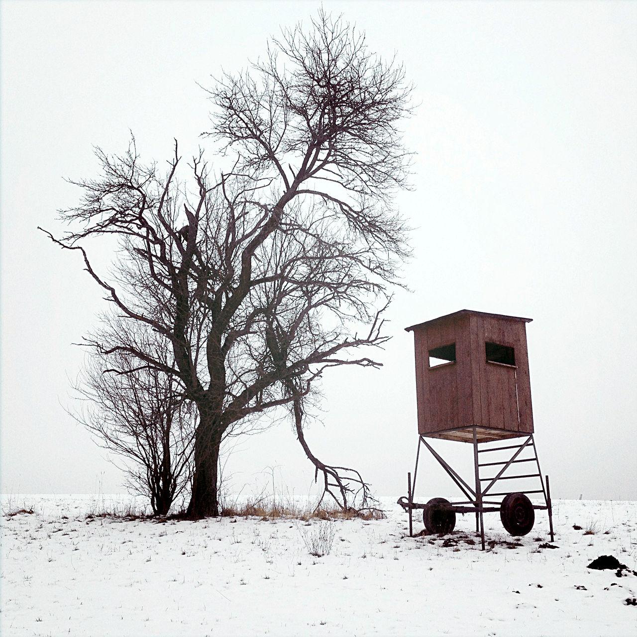 Ein Hochsitzwagen mit braunem Aufbau in Schneelandschaft. Dahinter ein kahler Obstbaum vor weißem Himmel