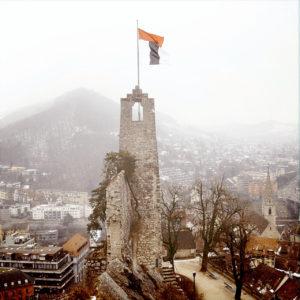 Ein schmaler Burgturm über einer kleinen, vernebelten Stadt. Am Bergfried weht eine Fahne.