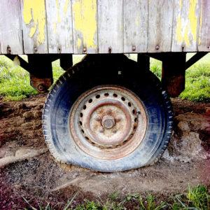 In der Bildmitte steht ein platter Reifen eines Bauwagens im Schlamm. Der Aufbau nimmt das obere Drittel des Bilds ein