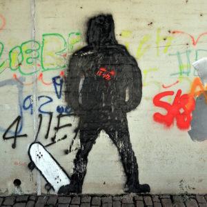 Eine Graffiti-Wand mit Hauptmotiv der schwarzen, gesprayten Silhouette eines vermummt wirkenden Skaters, der den Fuß links auf einem aufgestellten Skateboard zeigt. Daneben zahlreiche Tags und Schriftzüge.