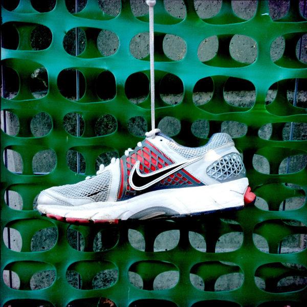 Ein Turnschuh der Marke Nike an einem grünen Kunststoff-Waben-Bauzaun hängend.