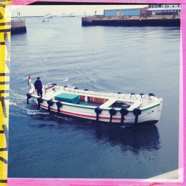 Mit buntem Hipstamatic-Rahmen umgeben zeigt das quadratische Bild ein Motorboot, das von links quert. Ein einsamer Mann an der Ruderpinne.
