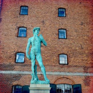 Eine kupfergrüne Skulptur, lebensgroß, stehend auf einem Sockel vor einem braunen Backsteinhaus mit zwei Spalten zu drei Reihen kleinen Segmentbogenfenstern.