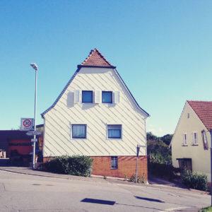 Ein Haus mit Krüppelwalmdach und vier großen und einem kleinen Fenster steht an einer von links nach rechts fallenden Straße.
