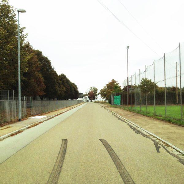In der Seitenstraße zwischen dem hohen Zaun eines Fußballplatzes und einem niedirgen Zaun links gegenüber endet eine pechschwarze Bremsspur im unteren Bilddrittel.