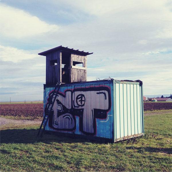Auf einem mit Graffiti bemalten Container thront ein hölzerner Jagshochsitz.