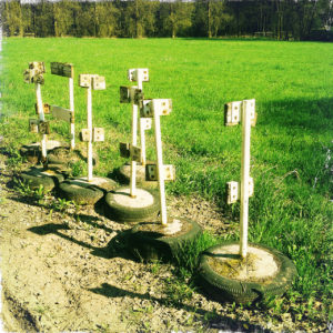Selbst gebastelte Absperrpfosten, deren Metallpfosten in Beton haften, der in alte Autoreifen gegossen wurden. Zehn Stück dicht gedrängt auf einer grünen Wiese zusammengeräumt.