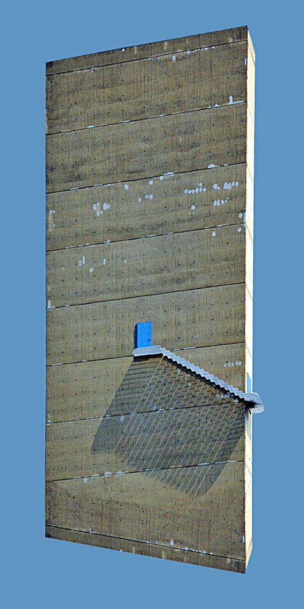 Aus einer Betonwand mündet eine Tür in eine Treppe. Das freigestellte Fassadenbild hat keinen Boden und scheint ähnlich wie ein Raumschiff vor blauem Hintergrund zu schweben. Die Treppe wirft einen langen Schatten an der Wand.