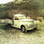 Ein Oldtimer Pritschenwagen mit Rundungen vor karger südländischer Felsen- und Krüppelbäumenkulisse