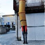 In der Röhre eines vielgliedrigen Bauschuttabfallrohres steht bis zu den Schultern sichtbar ein Mensch mit orangener Jacke und grauer Hose vor einer Hausbaustelle.