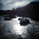 Bläuliche Gegenlichtaufnahme eines felsigen Katarakts. Die schrägstehende Sonne schimmert zwischen kleinen Felseninseln.