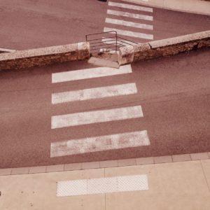 Blick auf den Ausschnitt zweier sich begegnender Serpentinen, über die ein Zebrastreifen führt, der die Mauer zwischen der Straße durchbricht und durch die Verschränkung der gegenläufigen Schrägen gebrochen wird.