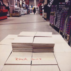 Der Blick schweift über einen Baumarkt-Einkaufswagen voller quadratischer Holzstücke entlang des weitläufigen zentralen Flurs des Geschäfts. Auf den Holzstücken klebt ein Zettel mit der Aufschrift Rinck 300x.