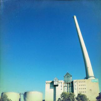 Am unteren Bildrand nimmt die betongemaserte Silhouette eines Industriebauwerks etwa ein Achtel bis ein fünftel des quadratischen Retrophotos ein. Nur ein Schlot ragt rechts im Bild bis fast zum oberen Bildrand in den von Tief blau bis blass cyan verlaufenden Himmel.