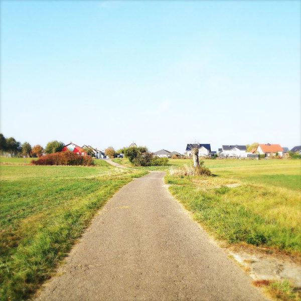 Straßenfoto eines geteerten Weges, der auf einen Dorfrand mit Neubauten hinzu führt.