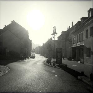 Gegenlichtaufnahme schwarz-weiß, einer kleinstädtischen Straßenflucht. Im Bildzentrum eine geschwungene Straßenlaterne, links ein wuchtiges Wohnhaus als Schattenriss und rechts eine Zeile Arbeiterhäuser dicht an dicht.