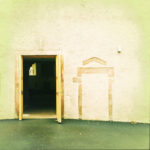 Eine Tür in einer alten Wand steht offen. Rechts daneben befindet sich eine zugemauerte Tür. Man blickt ins Dunkel einer historischen Kirche mit schmenhaftem Altar. Im Hintergrund schimmert ein Rundbogen der gegenüberliegenden Gebäudeseite.