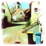 Neben zwei Mülltonnen führt eine gebogene Straße aufwärts zwischen Dorfhäusern hindurch auf eine kleine Kirche hinzu.