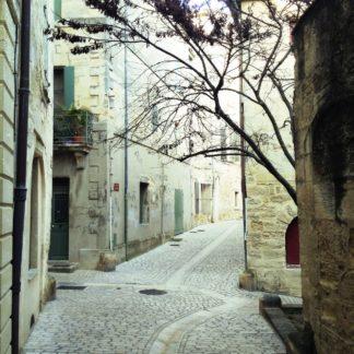 Eine steinerne, enge Stadtgasse mit verwinkeltem Innenhof, aus dem rechtsbildig einige Zweige eines winterkahlen mediterranen Bäumchens ragen und sich an die leichte Rechtsbiegung der Gasse schmiegen.