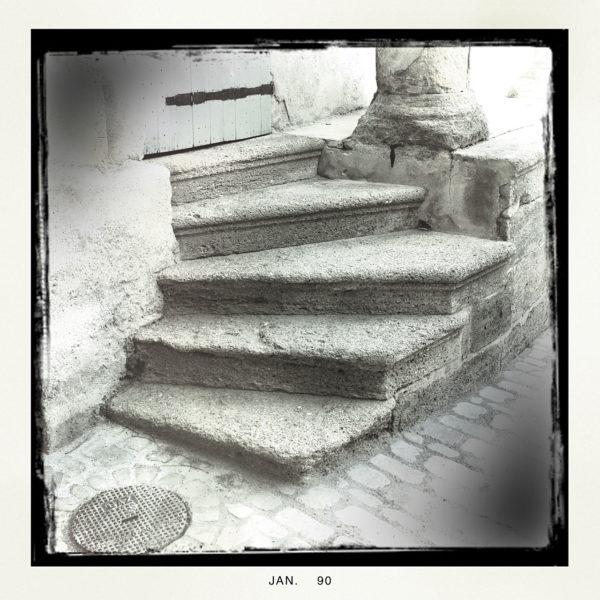 Linksgebogene, fünfstufige Steintreppe, schwarz gerahmt in vignettiertem Retro schwarz-weiß Foto. Unter dem Rahmen steht ein Datum Jan. 90