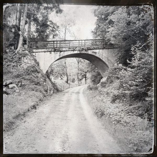 Fluchtperspektive entlang einer schnurgeraden ehemaligen Bahnstrecke auf eine Überführung hinzu. Schwarz-weiß-Bild.
