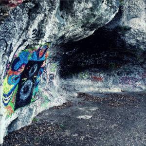 Eine kleine Felsenhöhle, die über und über mit Graffitis bemalt ist.