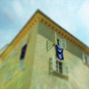 Froschperspektive auf ein Stadthaus, aus dessen Fenster eine Europaflagge hängt.