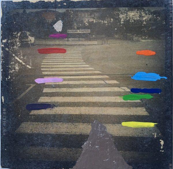 Retro-schwarz-weiß-Foto eines kurvenreichen Zebrastreifens, übermalt mit bunten kurzen Streifen rechts und links der Traverse.