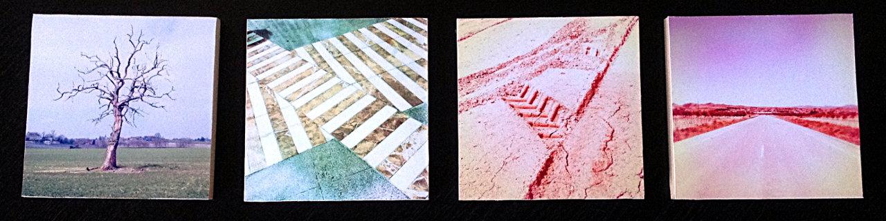 Vier quadratische Bilder nebeneinander auf schwarzem Untergrund. Von links: kahler Baum, zwei sich kreuzende Zebrastreifen farblich harmonierend in blau und grau, eine wie ein A aussehende Schlammspur, eine Straßenflucht im Flachland, beide auch farblich harmonierdend mit rötlicher Fehlfarbe.