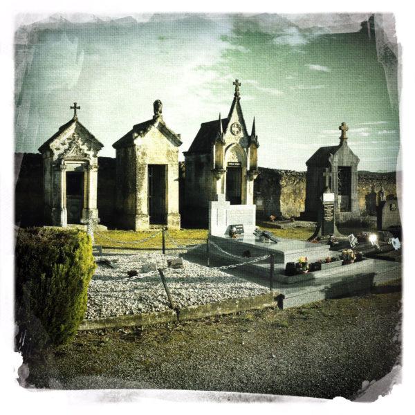 Vier Gruften am Rand einer Friedhofsmauer.