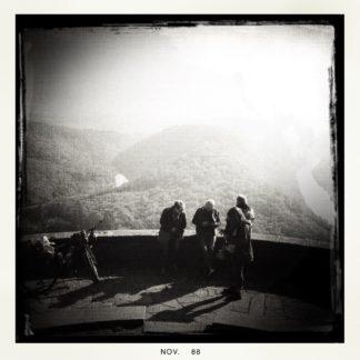 Schwarz-weiß-Aufnahme eines Aussichtspunkts über drei Personen, die vor einer kleinen Mauer stehen und über diese hinweg ins dunstige, gegenlichtige Tal blicken.