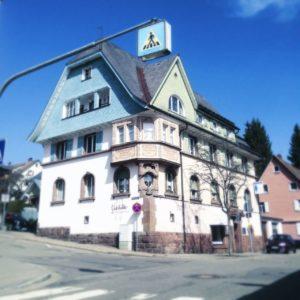 An langem Galgen hängt ein Zebrastreifenschild mitten über einer kleinstädtischen Kreuzung. Dahinter ein schwarzwäldisches Stadthaus mit Krüppelwalm und großem Erker.