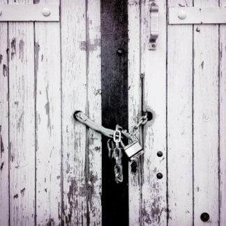 Schwarz-weiß Foto eines Brettertors, das mit einer Kette und Vorhängeschloss verschlossen ist. Detailaufnahme.