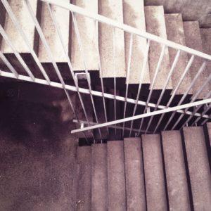 Blick in ein Treppenhaus auf die Gegenläufigkeit der Stufen und Geländer.