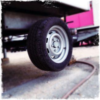Das kleine, gummibereifte Rad eines Jahrmarktswagens schwebt in der Luft. Ein Schlauch schlängelt sich über den Boden. Im Hintergrund ein lila Jahrmarktwagen.