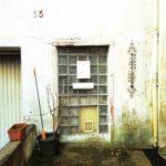 Eine mit Glasbausteinen vermauerte ehemalige Türöffnung. Unten eine Katzenklappe, mittig ein Briefkasten.