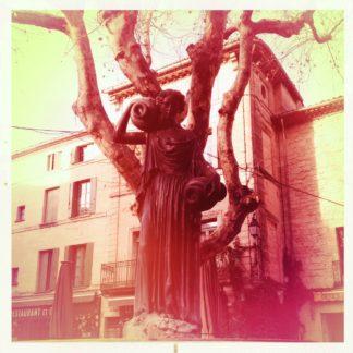 Rötliches Retrobild, quadratisch, einer Skulptur vor einer innerstädtischen Platane und Hauswand.