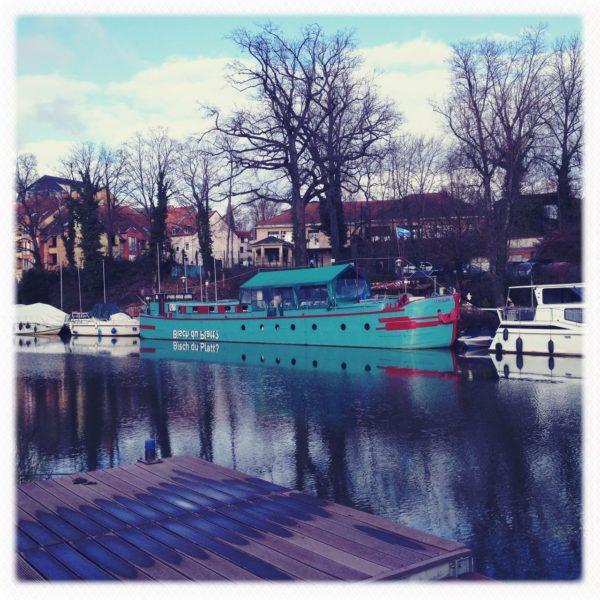 Ein kupferoxidgrünes Schiff am anderen Ufer eines Flusses verträut. Der Schriftzug 'Bisch du platt?', spiegelverkehrt auf dem Rumpf, ist auf der Wasseroberfläche lesbar.