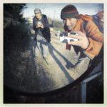 Ein Mann und eine Frau, die sich in einem Straßenspiegel selbst fotografieren bücken sich ins Bild. Lange Schatten laufen in den blassen Hintergrund