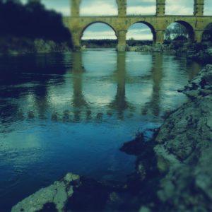 Die unteren Dreiviertel des Bildes zeigen einen bläulich schimmernden, die Landschaft schemenhaft spiegelnden Fluss, flankiert von Felsen und Uferbewuchs. Wie aufgepfropft thronen die Bögen eines römischen Aquädukts und enden plötzlich am oberen Bildrand.