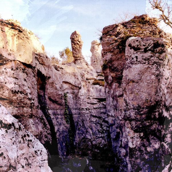 Eine Felsengegend, bräunlich mit runzeligen Kalkfelsen. Eine kleine Schlucht öffnet sich, in der bildmittig ein fingerähnlicher Fels herausragt.