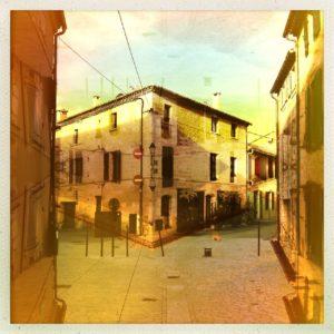 Gespiegelte Überblendung einer städtischen, südfranzösischen Straße. Das symmetrisch wirkende Bild hat einen gelblich ockerfarbenen Grundton. Die strenge Linienführung aus diagonalen und senkrechten Gebäudeformen erzeugen eine harmonische Flächenaufteilung.
