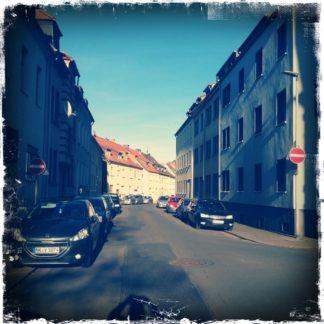 Die gewundene Stadtstraße führt durch lückenlos bebaute dreistöckige Wohnhäuser. Im schrägen Sonnenlich schimmert die rechte Häuserphalanx.