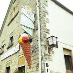 Riesige Eistüte mit vier sichtbaren Bällchen von fünf. Gelb, rot, grün und oben weiß an einer Hausecke in Höhe des ersten Stocks angebracht. Daneben Hausnummer 19 und eine Gaststättenbeleuchtung.