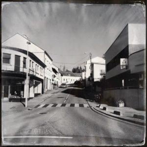 Schwarz-weiß-Aufnahme einer kleinstädtischen Straßenmündung. Links ein Rundbau, rechts eine Art Parkhaus. Ein Zebrastreifen quert.