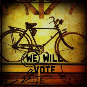 Gelblich schimmernder Hintergrund mit einem alten Fahrrad im Profil. Darunter der Schriftzug We Will Vote