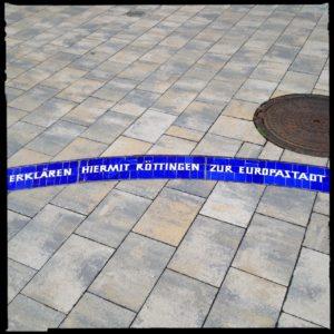 Im rechteckigen Pflaster eines Dorfplatzes ist ein blauer Bogen aus Keramikfließen eingearbeitet mit der weißen Schrift 'Erklären hiermit Röttingen zur Europastadt. Obendrüber wie ein Planet ein gusseiserner Kanaldeckel.
