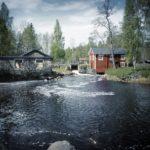 Ein Bach mündet über ein kleines Wehr zwischen einem roten Holzhaus und einem Steinernen Bau in einen aufgewühlten, schwarzblauen See.