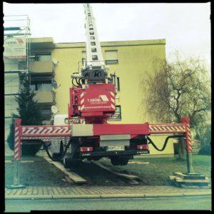 Ein fahrbarer Krand mit ausgefahrenen hydraulischen Stützen vor einem Flachdach-Mietshaus. Das rote Fahrzeug scheint wie zu fliegen. Die Räder hängen in der Luft.