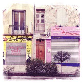 Fehlfarben Retrobild einer kleinstädtischen Häuserfront in Frankreich. Die Fenster der Läden sind mit schweren, eisernen Rolläden verhangen. Man liest Auto-Moto Ecole Castor und Atres & Flamme